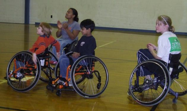 Anjali cheering on three young kids playing wheelchair basketball