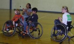 Three kids in wheelchairs on an indoor basketball court with Anjali.